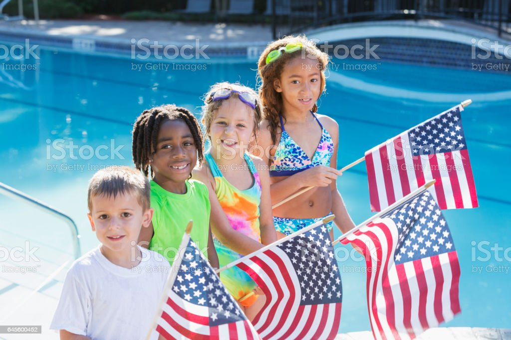 Multi-ethnic children at pool holding American flags stock photo