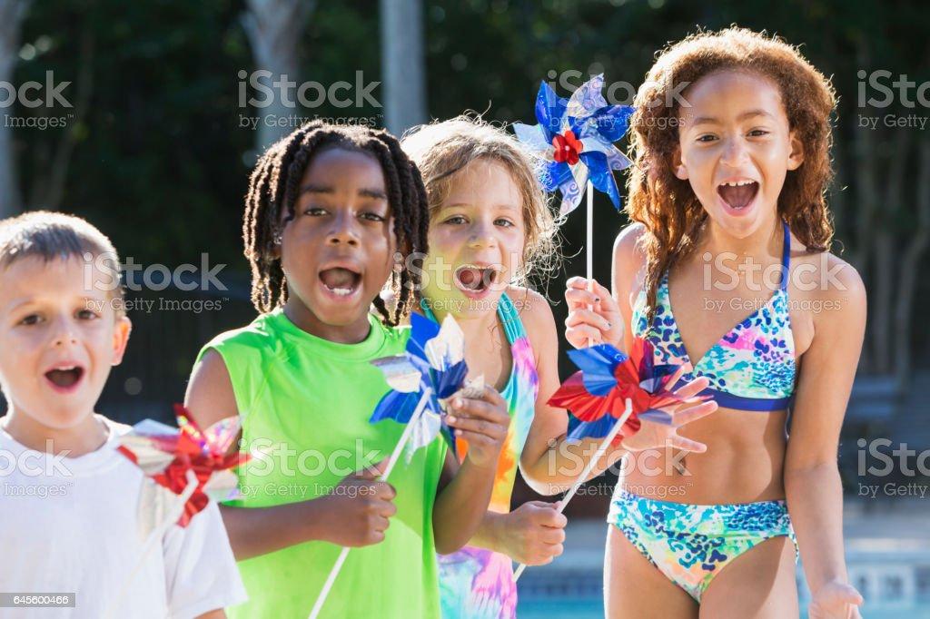 Multi-ethnic children at pool holding pinwheels stock photo