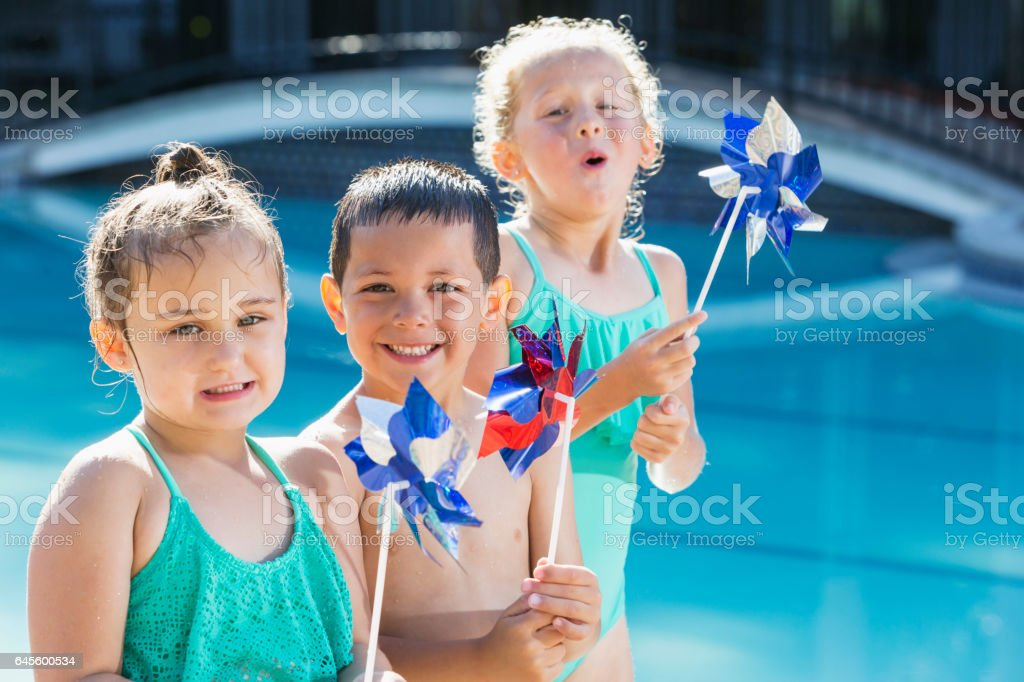 Multi-ethnic children at pool playing with pinwheels stock photo