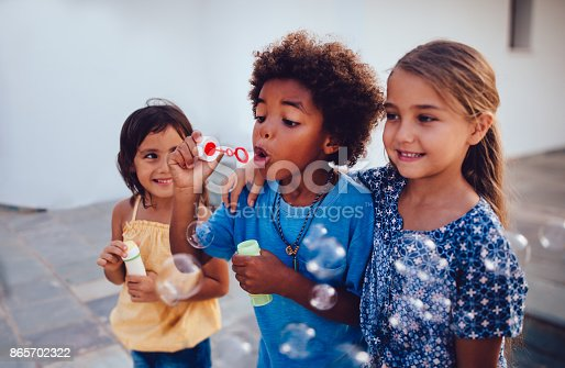 istock Multi-ethnic children best friends blowing bubbles on summer holidays 865702322