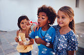 Group of multi-ethnic children best friends having fun blowing bubbles on summer vacations