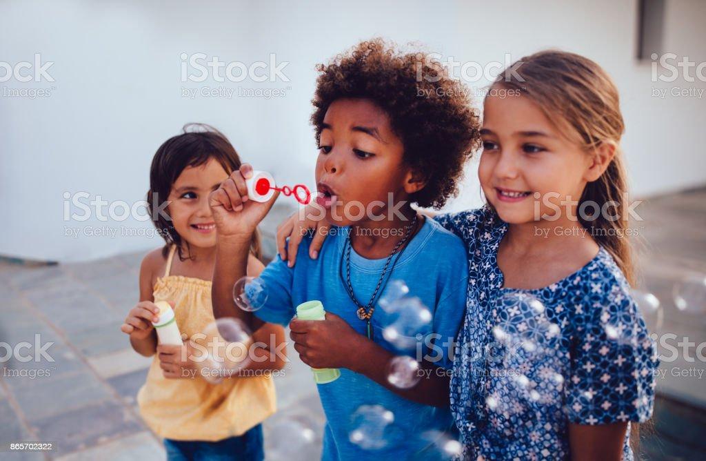 多族裔兒童最好的朋友在暑假上吹泡泡圖像檔