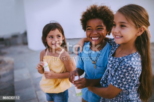 istock Multi-ethnic children best friends having fun with bubbles in summer 865030112