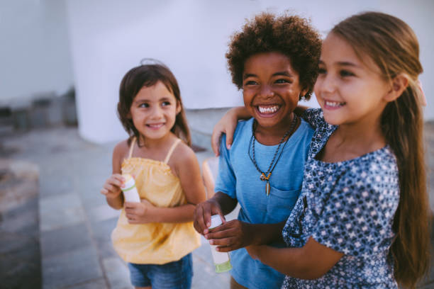 Multi-ethnic children best friends having fun with bubbles in summer stock photo