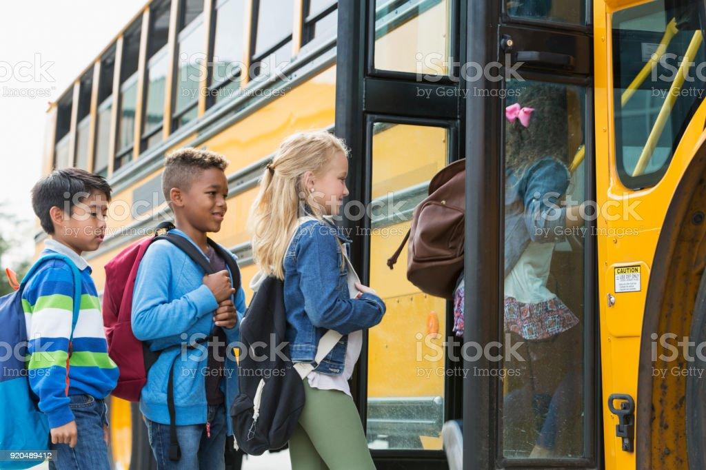Multi-étnica crianças embarcando um ônibus escolar - foto de acervo