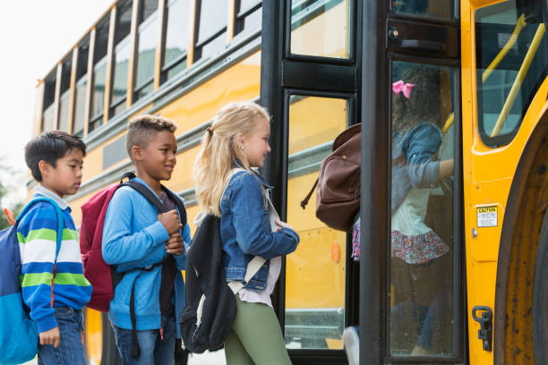 multi-ethnic children boarding a school bus - school bus stock photos and pictures