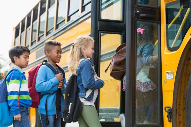multiethniques enfants monter dans un autobus scolaire - bus scolaires photos et images de collection