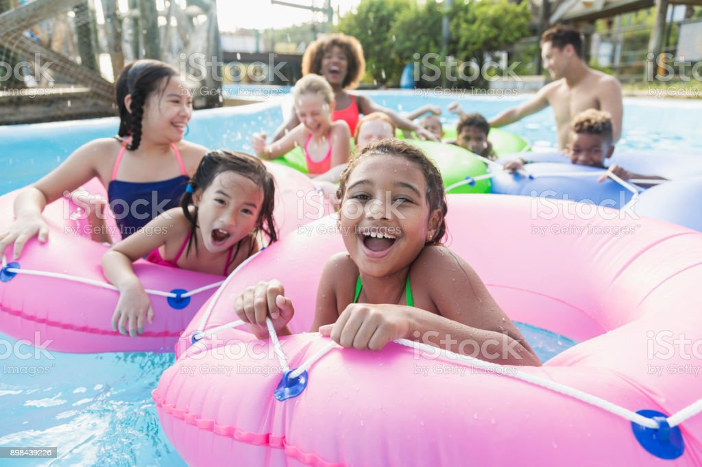 Multi-ethnic children, fun on lazy river at water park stock photo
