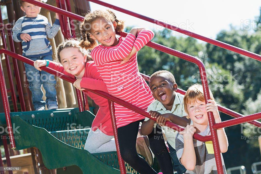 Multi-ethnic children having fun at playground stock photo