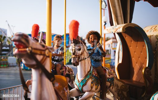 Multi-ethnic mixed family brother and sister having fun riding horses on amusement park carousel ride
