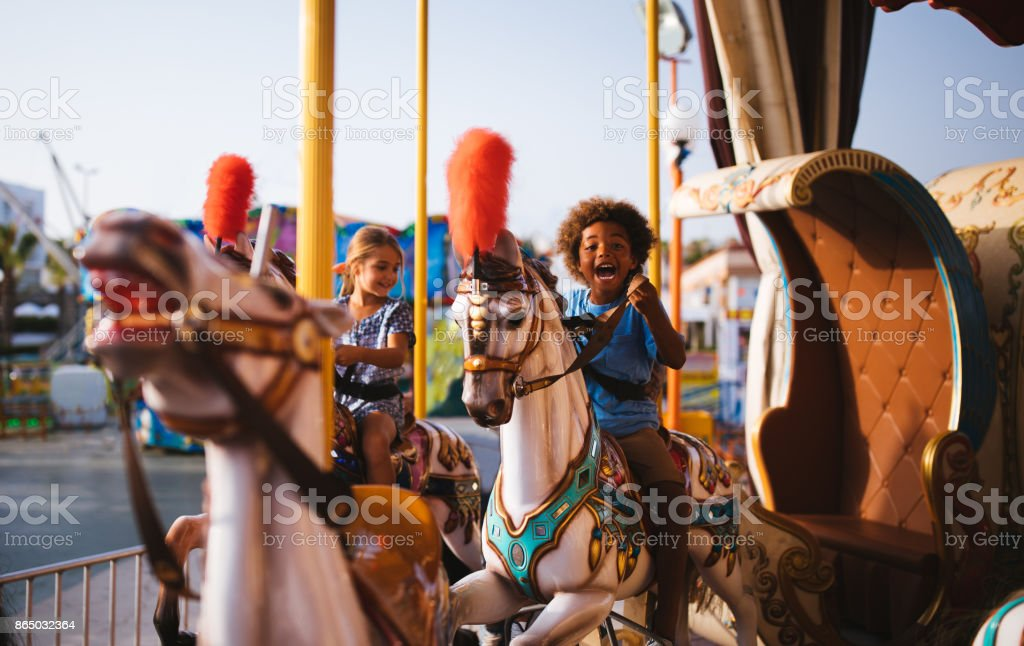 Multi-ethnic children having fun on funfair merry-go-round carousel ride stock photo