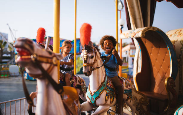 Multi-ethnic children having fun on funfair merry-go-round carousel ride Multi-ethnic mixed family brother and sister having fun riding horses on amusement park carousel ride carnival children stock pictures, royalty-free photos & images