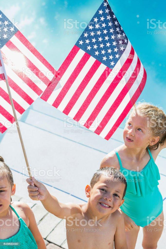 Multi-ethnic children holding American flags stock photo