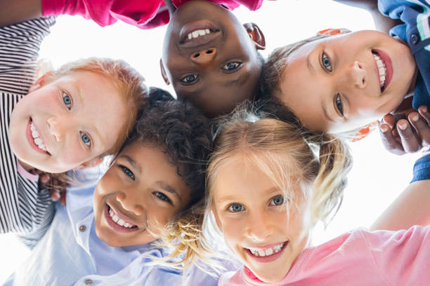 Multiethnic children in a circle Closeup face of happy multiethnic children embracing each other and smiling at camera. Team of smiling kids embracing together in a circle. Portrait of young boy and pretty girls looking at camera. 8 9 years stock pictures, royalty-free photos & images