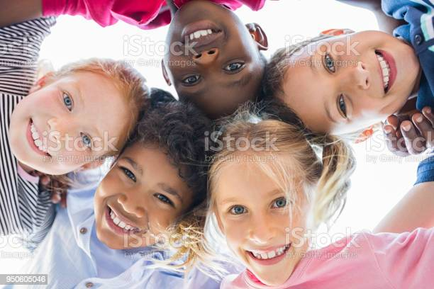 Closeup face of happy multiethnic children embracing each other and smiling at camera. Team of smiling kids embracing together in a circle. Portrait of young boy and pretty girls looking at camera.