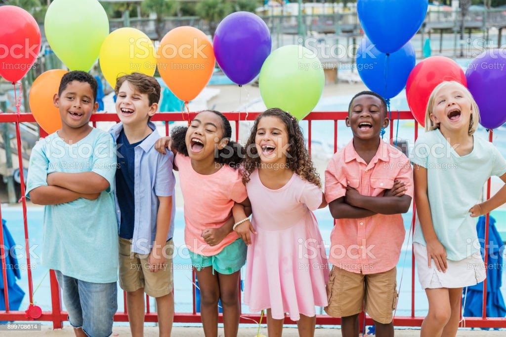 Multi-étnica crianças rindo, balões coloridos - foto de acervo