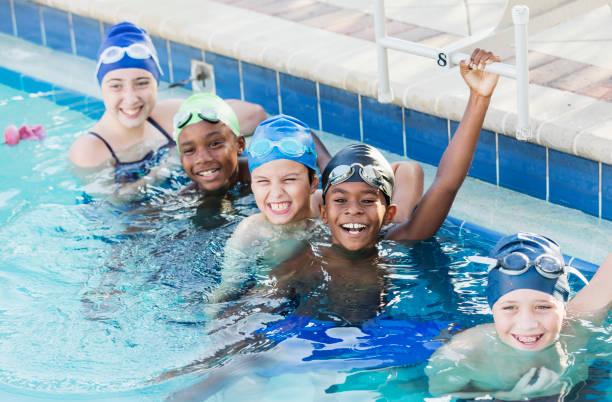 Multi-ethnic children on swim team in pool stock photo
