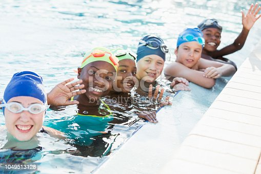 A multi-ethnic group of six boys and girls on a swim team, wearing swim caps and goggles on their heads, in the water at the side of the swimming pool. The children are 9 to 12 years old. The focus is on the African-American girl, second from the left, smiling and waving at the camera.