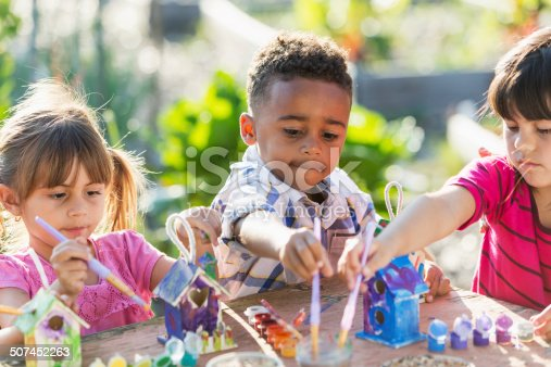 A multiracial group of three serious young children doing an arts and crafts project, painting little wooden bird houses for Earth Day.  It is a bright, sunny day and they are sitting at a wooden table reaching with their paintbrushes.  An African American boy, 5 years old, is sitting in the middle between two Hispanic girls.