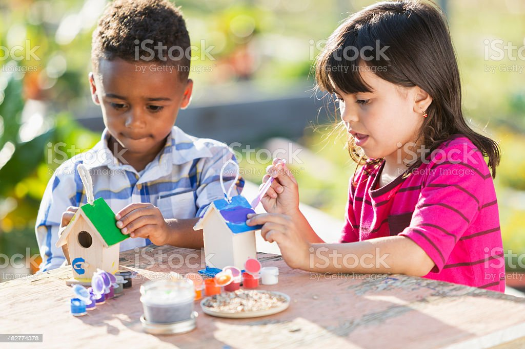 Multi-ethnic children painting little wooden bird houses stock photo