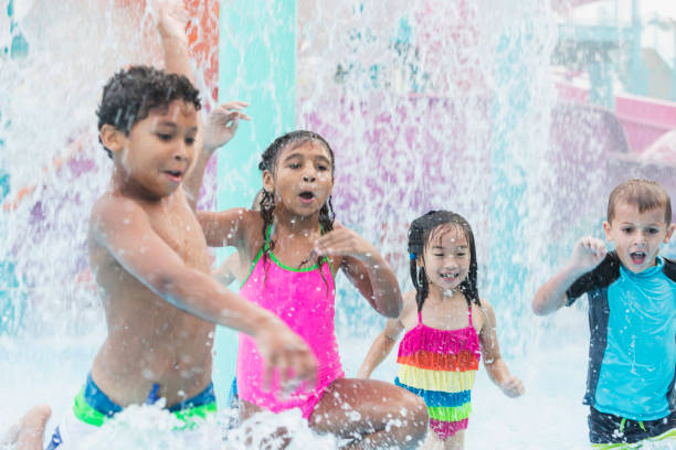 Multi-ethnic children playing in falling water at park stock photo