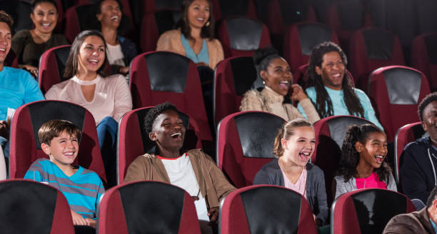 Multi-ethnic children, teens, young adults in theater stock photo