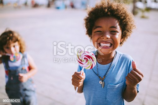 Happy multi-ethnic mixed family little boys eating lollipops in summer in the city