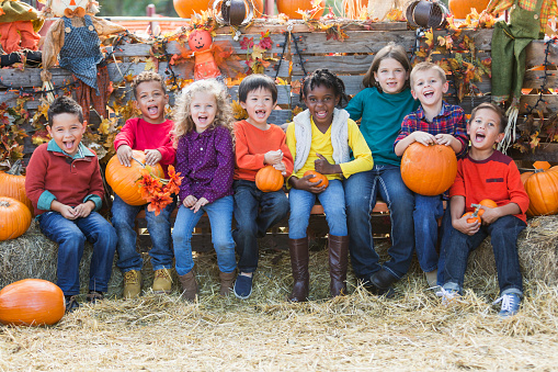 A group of eight multi-ethnic children sitting in a row surrounded by pumpkins, scarecrows and hay. They are at a fall festival celebrating autumn.