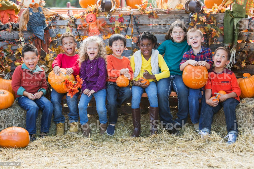 Multi-ethnic children with pumpkins at fall festival stock photo
