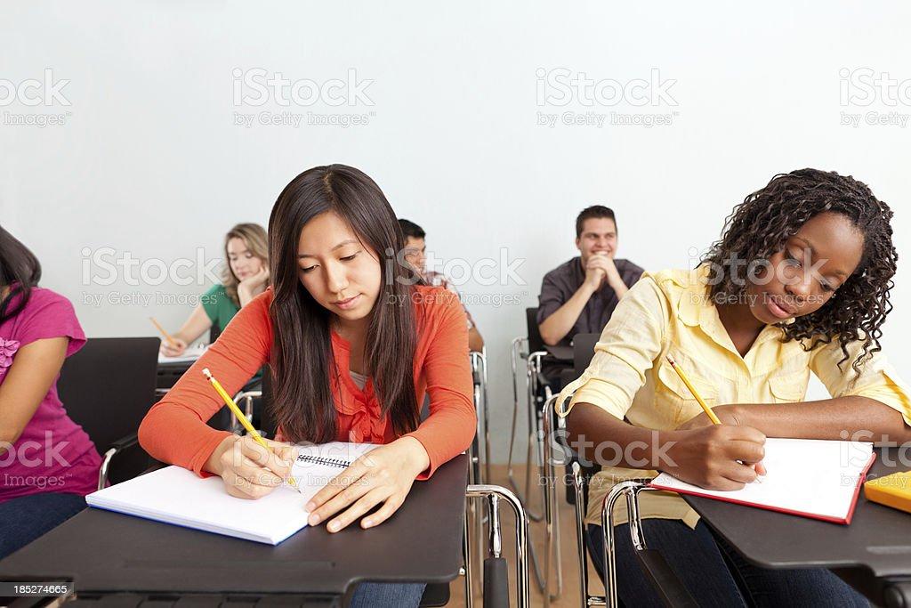 Multi-ethnic classmates taking notes royalty-free stock photo