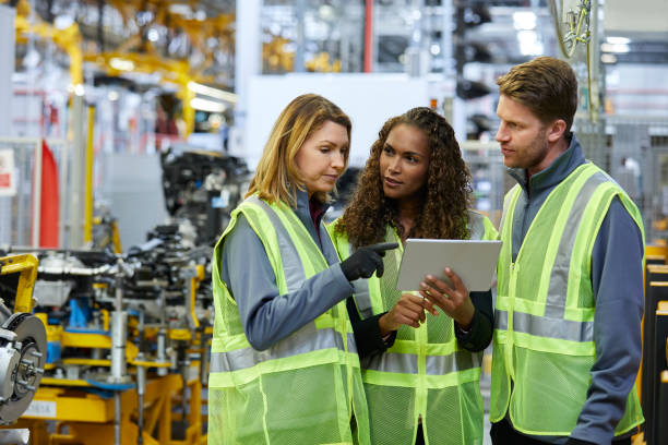 Multi-ethnic colleagues discussing over tablet Multi-ethnic colleagues discussing over digital tablet at factory. Confident mechanical engineers are standing at automobile industry. They are wearing reflective clothing. mechanical engineering stock pictures, royalty-free photos & images