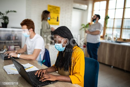 1124783373 istock photo Multi-ethnic colleagues with protective face masks using laptops at modern office 1250025715