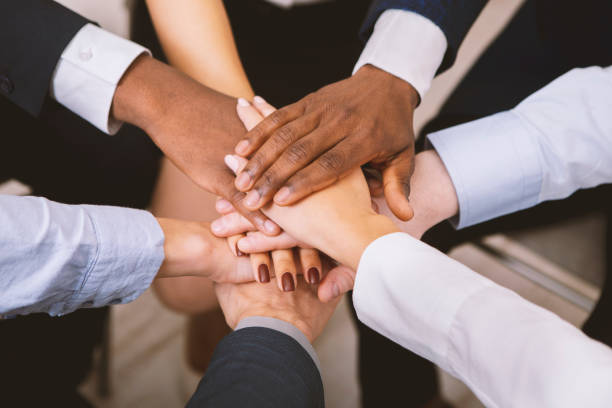 Multiethnic corporate teame stacking hands together in office Business unity. Multiethnic corporate teame stacking hands together in office, close up place of work stock pictures, royalty-free photos & images