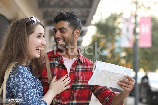 Multi-ethnic couple on vacation in downtown city area.  They hold city map.