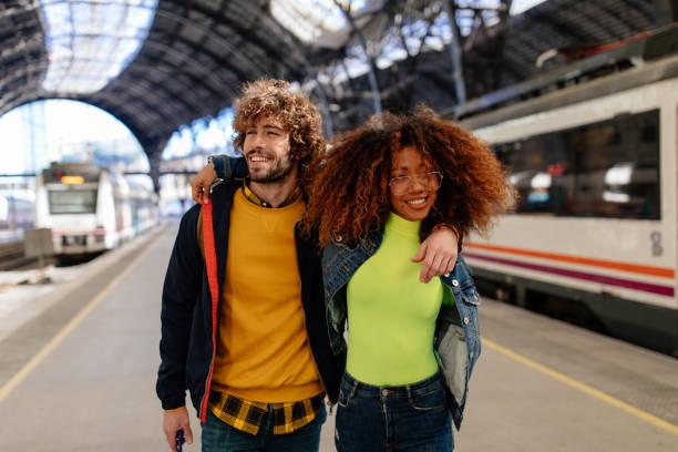 Tren istasyonunda platformda birbirlerini kucaklayan çok ırklı çift stok fotoğrafı