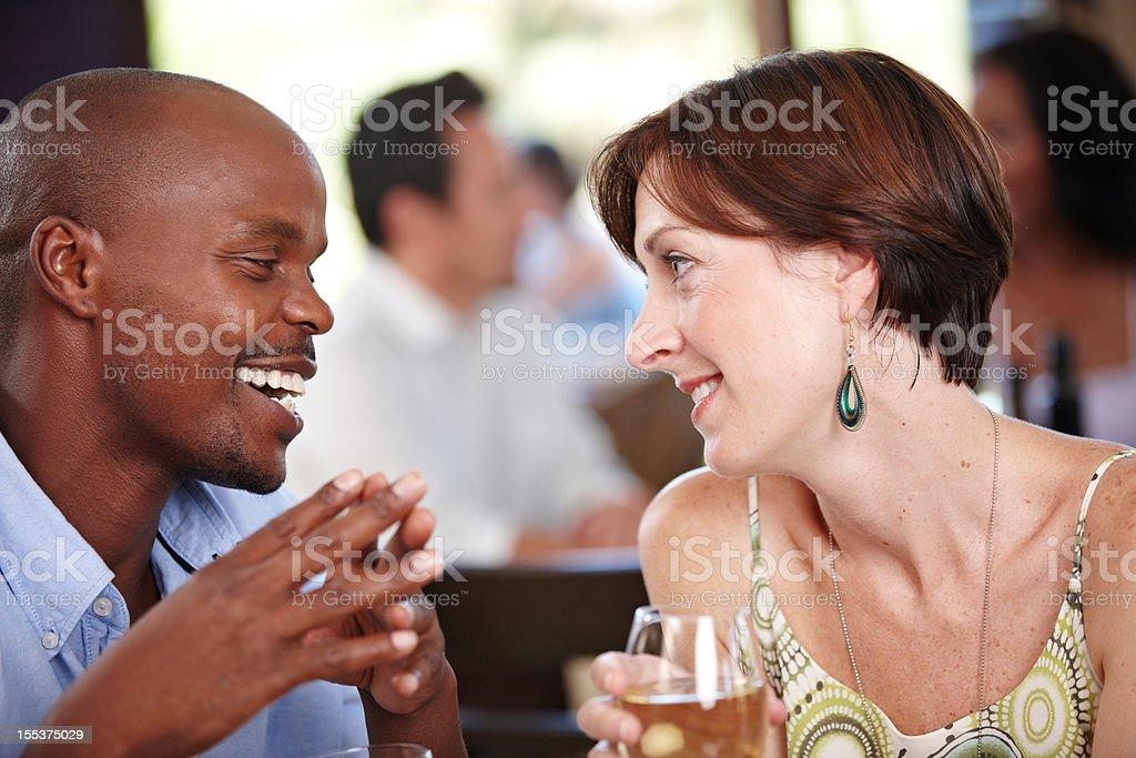 Multi-ethnic couple enjoying intimate conversation royalty-free stock photo