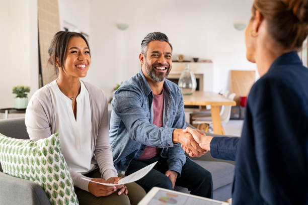 Multiethnic couple handshake with consultant at home stock photo