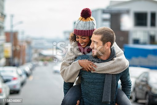Smiling man giving piggyback ride to woman in the city. Young multiethnic couple in cold clothes walking in street and having fun. Cheerful girlfriend with wool cap and boyfriend in sweater enjoying winter together outdoor.