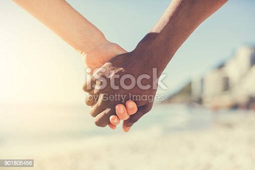 Multi-ethnic couple holding hands. Cropped image of man and woman are at beach. They are spending leisure time on sunny day.