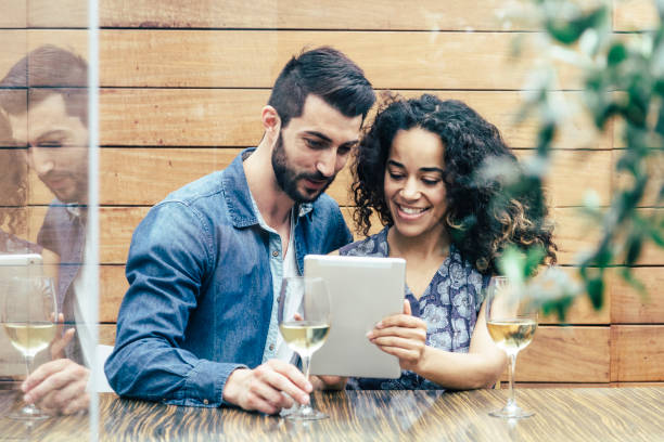 Multiethnic couple in a restaurant looking at tablet stock photo