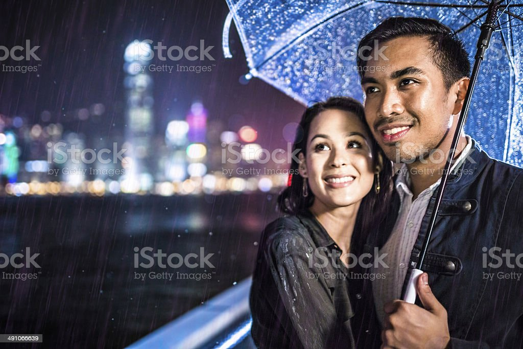 Multi-ethnic couple in Hong Kong under the rain stock photo