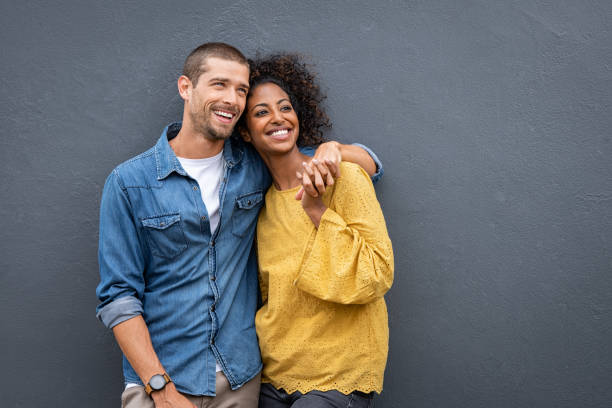 multiethnic couple in love standing and holding hands - future hug imagens e fotografias de stock