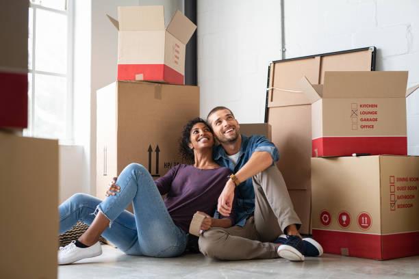 Multiethnisches Paar in neuem Zuhause mit Boxen – Foto