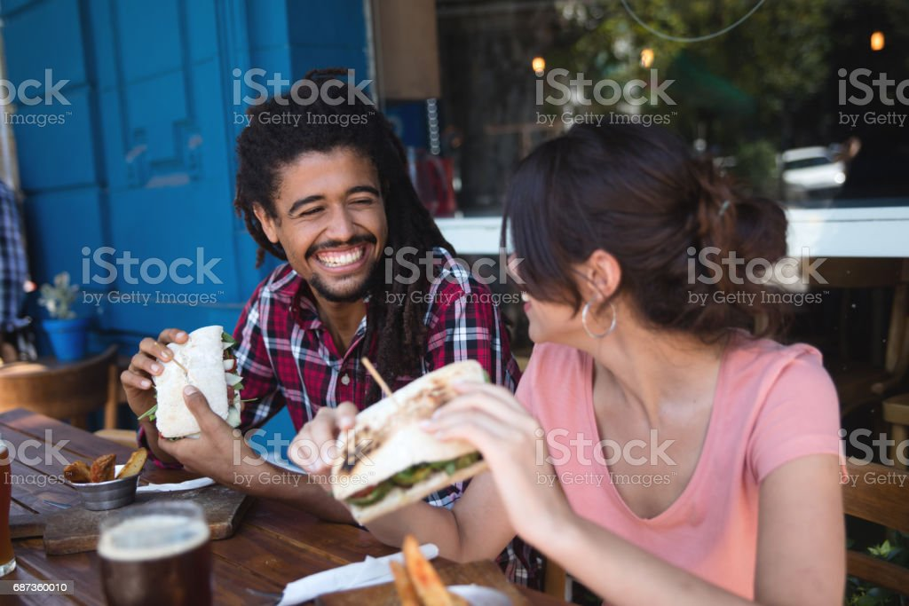 Multi-ethnic couple laughing while eating at a cafe stock photo