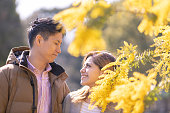 Multi-ethnic couple looking at each other in Mimosa blossoms