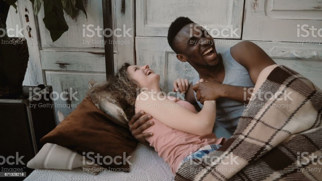 Multiethnic couple lying on bed, la holding their hands. Male and female look happy. Man and woman enjoy time together stock photo