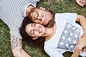 Portrait of happy man and woman relaxing in back yard. Directly above view of smiling multi-ethnic couple is lying on grass. They are in casuals.