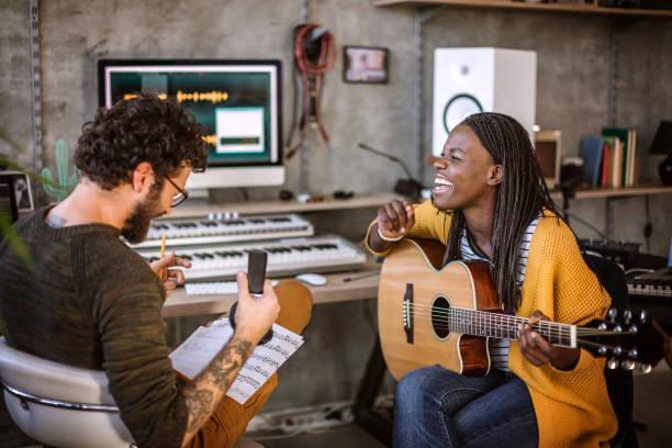 multiethnisches paar beim musizieren im tonstudio - musiknoten tattoos stock-fotos und bilder