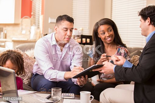 994164754 istock photo Multi-ethnic couple meets with financial advisor. 1151422164