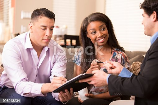 994164754 istock photo Multi-ethnic couple meets with financial advisor. 926243234